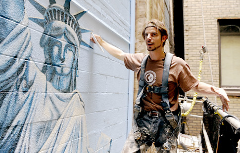 """Artist Patrick Ganino labors on his painting of a three-story tall Statue of Liberty, part of a 12-story high mural going up in the courtyard of two neighboring downtown Brooklyn towers."""" title=""""Artist Patrick Ganino labors on his painting of a three-story tall Statue of Liberty, part of a 12-story high mural going up in the courtyard of two neighboring downtown Brooklyn towers."""